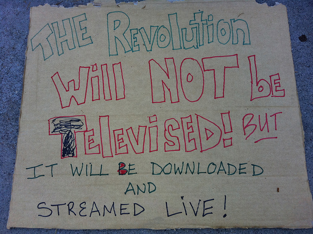 A handwritten protest sign, reading: The revolution will not be televised but it will be downloaded and streamed live