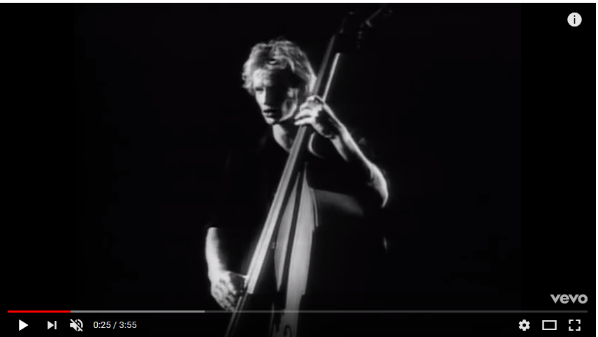 """Black and white video image of a bass player from the music video for """"Every Breath You Take"""" by the Police."""